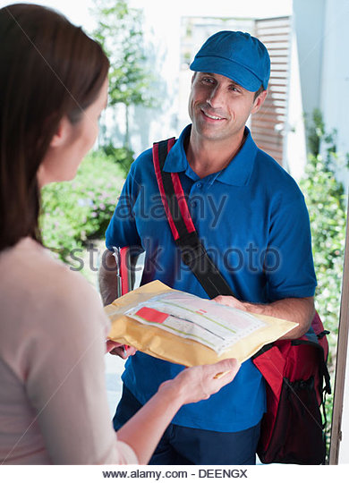 Male delivery person giving package to woman - Stock Image