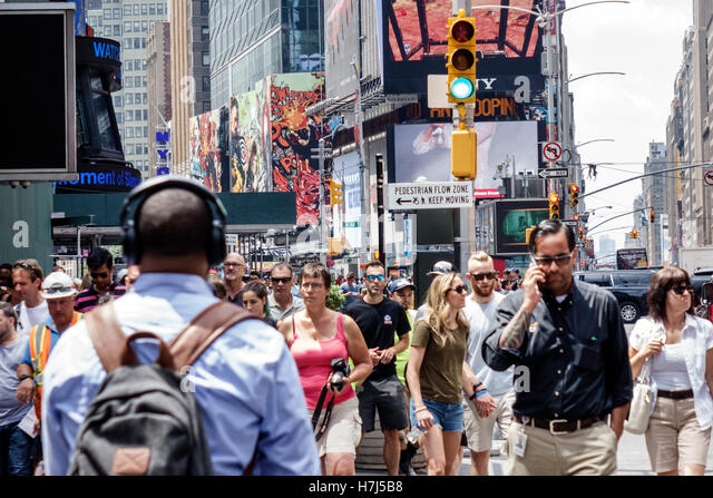Manhattan New York City NYC NY Midtown Broadway Times Square pedestrian crowd billboards street crossing man woman - Stock Image