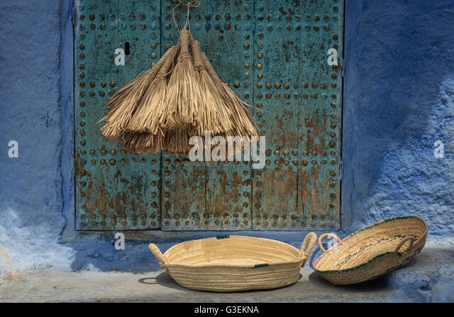 Still life of natural straw brooms and two baskets against old, blue door. - Stock Image