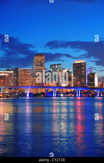 Miami city skyline panorama at dusk with urban skyscrapers and bridge over sea with reflection - Stock Image