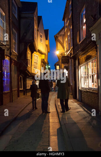 A family in The Shambles in York, at night.. This famous street is very popular with tourists. - Stock Image