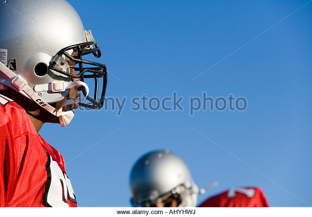Two American football players wearing red football strips and protective helmets, standing against clear blue sky - Stock Image