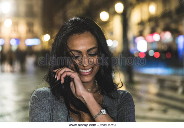 Portrait of young woman in city at night, laughing, Lisbon, Portugal - Stock-Bilder