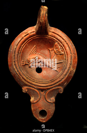 Symbols of the sea god Poseidon (The dolphin is the boon companions of the sailors) Oil Lamp 100 AD Roman - Stock Image