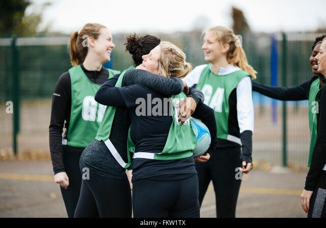 Female netball team celebrating on netball court - Stock Image