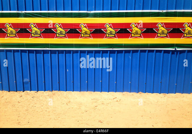 Zimbabwe flag banner along a blue corrugated wall - Stock Image