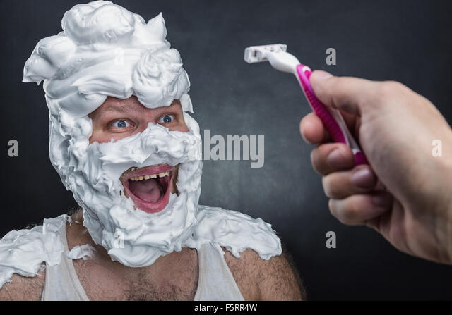 Surprised man with shaving foam on his face over grey background - Stock Image