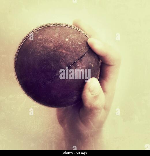 Cricket ball caught in a boys hand - Stock Image