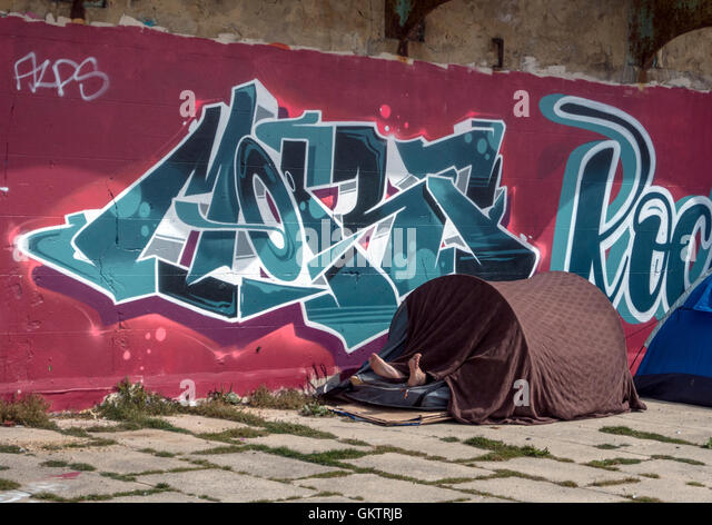 Two feet short: living rough under a short tent on Brighton seafront, England - Stock Image