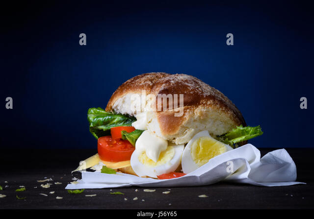 Delicious burger with egg, tomato, cheese, lettuce and mayonnaise on wooden counter. Copy space. - Stock Image