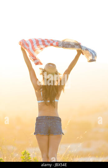 Woman wearing bra top and denim shorts, holding American flag above head, rear view - Stock-Bilder