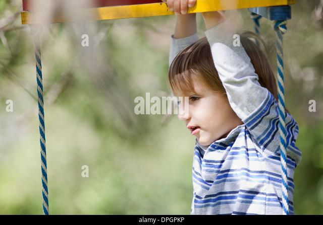 Boy playing on jungle gym - Stock-Bilder