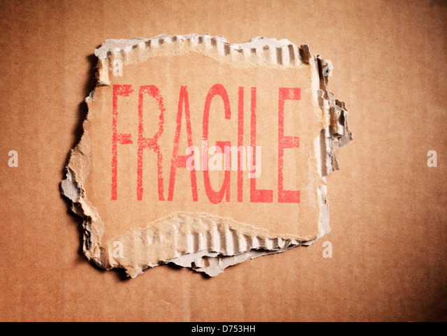 Word Fragile stamped on a piece of brown corrugated cardboard. - Stock Image