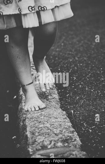 Low Section Of Girl Walking On Retaining Wall - Stock Image