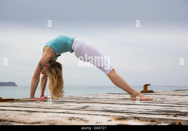 Mid adult woman bending over backwards practicing yoga on wooden sea pier - Stock Image
