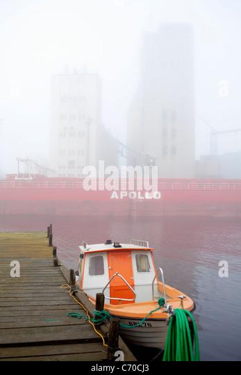 Tugboat docked in urban bay - Stock-Bilder