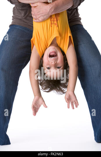 Little Boy Hanging Upside Down On White Background on white background - Stock Image