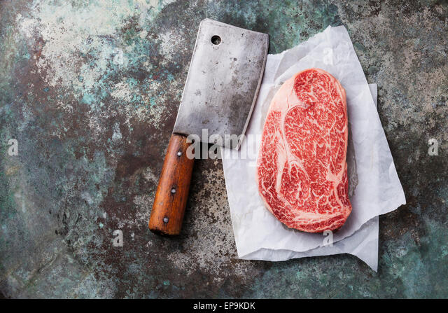 Raw fresh marbled meat Black Angus Steak Ribeye and meat cleaver on metal background - Stock Image