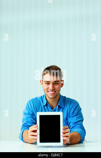 Young businessman showing display of tablet computer - Stock Image