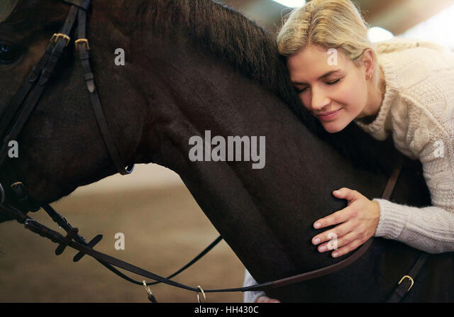 londe female with eyes closed hugging dark horse - Stock Image