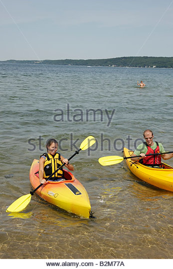 Michigan Traverse City West Arm Grand Traverse Bay Clinch Park kayak man woman water sport activity recreation oars - Stock Image