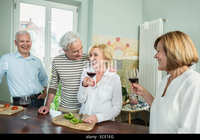 Senior group friends preparing lunch drinking wine - Stock Image