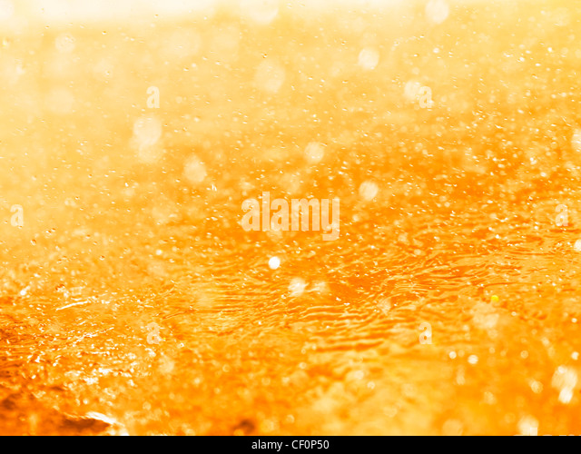 Orange splashing liquid closeup abstract background texture - Stock Image