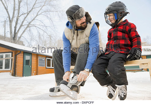 Father and son getting ready to skate - Stock Image