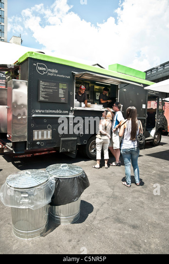 happy customers line up at falafel food truck in lot next to High Line elevated park entrance Chelsea neighborhood - Stock Image