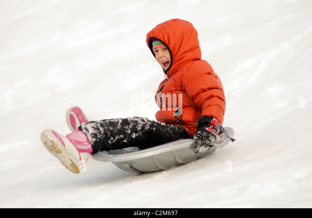 Girl sliding down a city park hill in the winter age 7. St Paul Minnesota MN USA - Stock Image