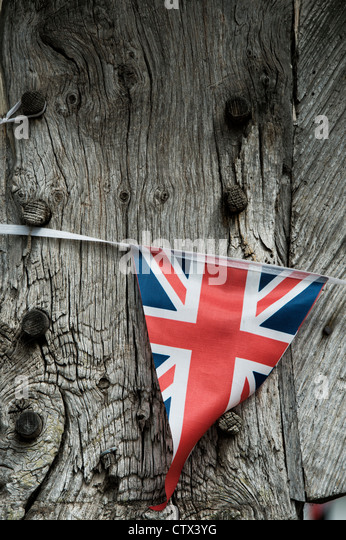Union Jack bunting on a old wooden oak house beam. Pembridge. Herefordshire. England - Stock Image
