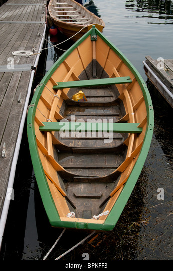 Traditional 'Pilot Gig', a hand made wooden rowing boat at a pier in Gloucester, Massachusetts. - Stock Image
