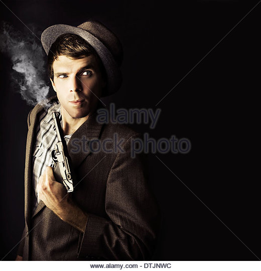 Dark Studio Image Of A Professional Hit Man Wearing Vintage Suit Holding A Retro Hand Gun In A Dangerous Business - Stock Image