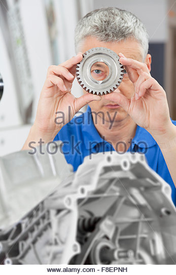 Portrait of engineer peering through gear wheel with engine block in foreground - Stock Image