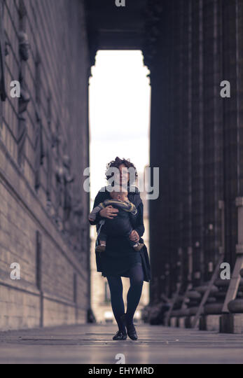Mid adult woman carrying her son, Paris, France - Stock Image