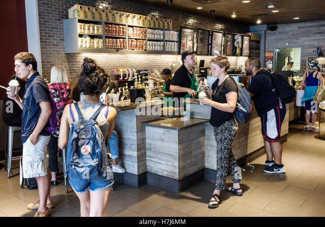 Manhattan New York City NYC NY Upper East Side Starbucks Coffee counter man woman customers barista cashier young - Stock Image