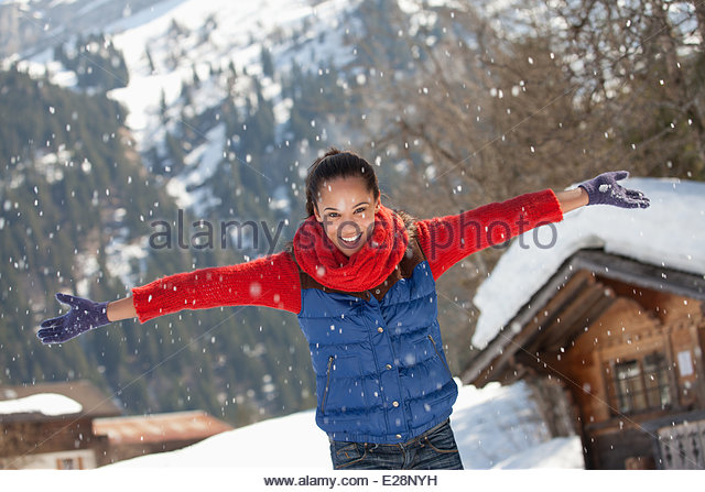 Happy woman throwing snow - Stock Image