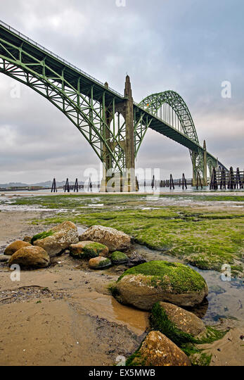 Rocks, moss and Yaquina Bay Bridge, Newport, Oregon USA - Stock Image