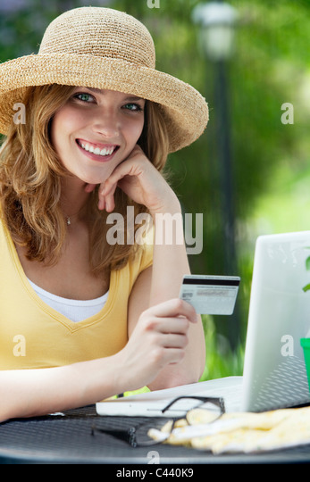 Smiling woman shopping online with credit card and laptop outside - Stock Image