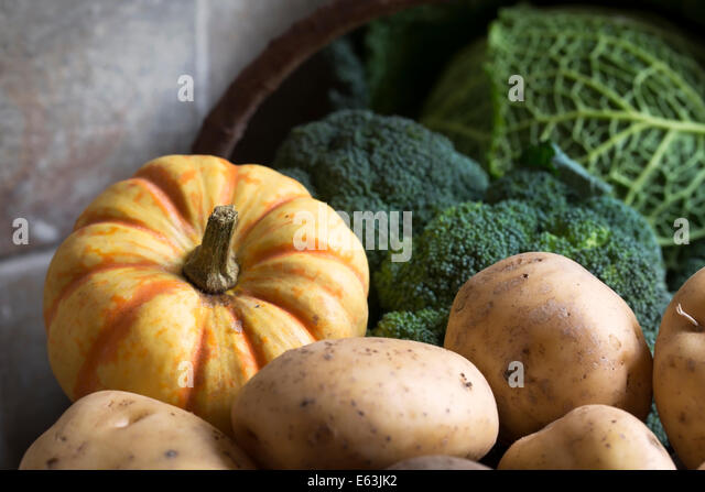 Basket of winter vegetables including broccoli, sweet lightning squash and potatoes. - Stock Image