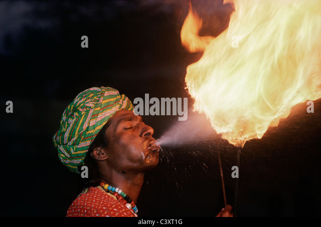 Indian fire eater blows flames during a street performance. New Delhi, India - Stock-Bilder