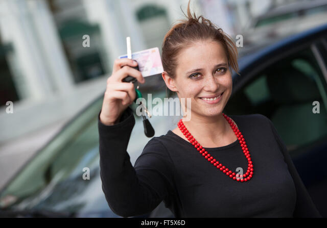 Smiling young woman behind the car showing her driver's license and keys - Stock Image