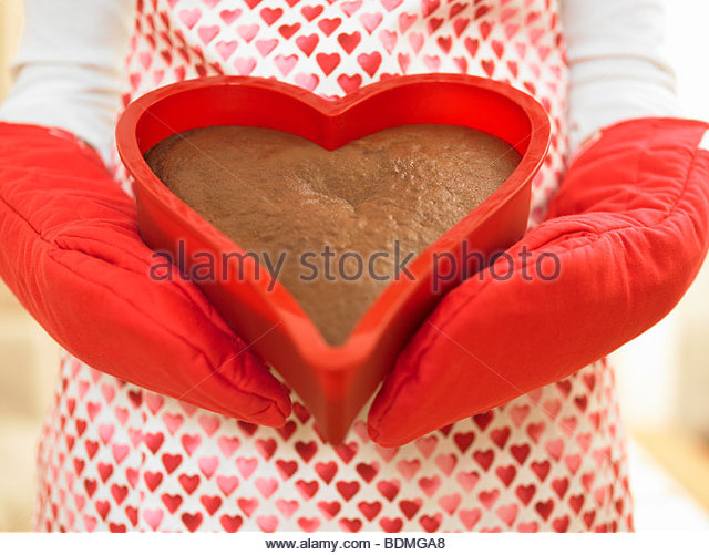 Close up of woman holding heart-shaped cake - Stock Image