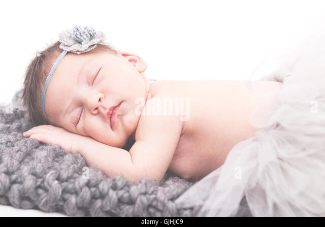 Portrait of a newborn baby girl sleeping on blanket - Stock Image