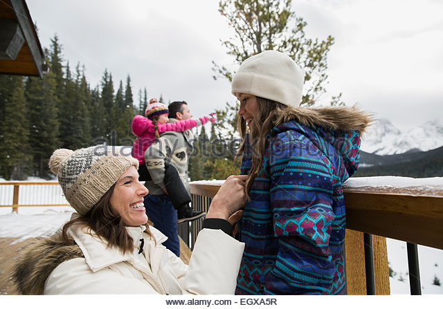 Mother helping daughter with coat on snowy deck - Stock Image
