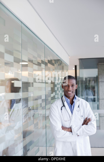 Doctor standing in hospital corridor with arms folded - Stock Image