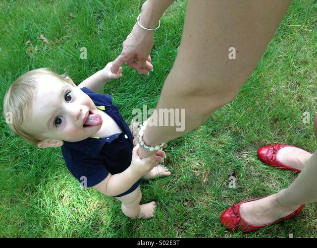 Baby boy's first steps with mom in summer. - Stock Image