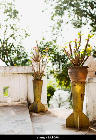 Shells from US made bombs act as flower pot holders near a walkway at Mt. Phou Si. Luang Prabang, Laos. - Stock Image