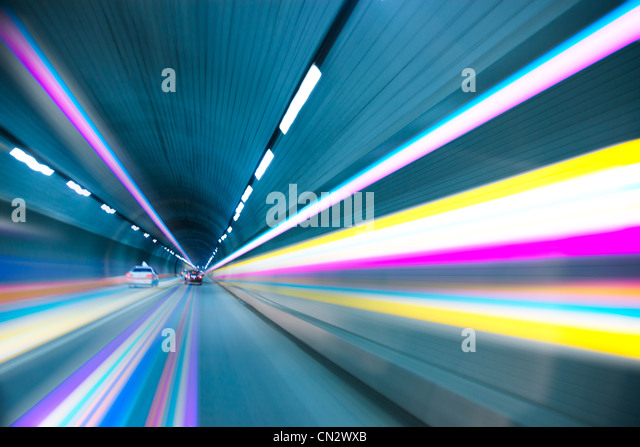 Abstract speed motion in urban highway road tunnel, blurred motion toward the light - Stock Image