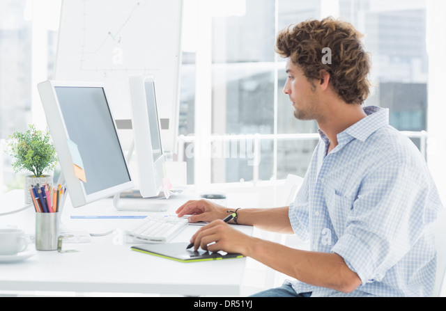 Male artist drawing something on graphic tablet with pen - Stock Image